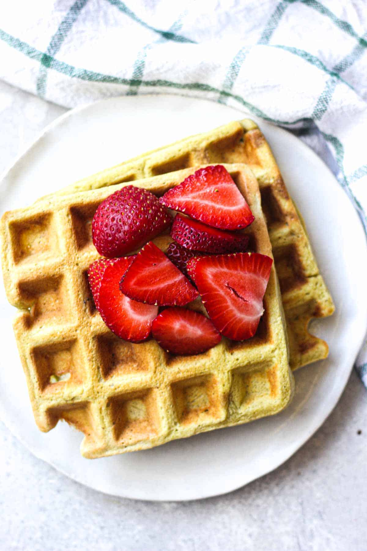 two waffles on a plate with sliced strawberries on top