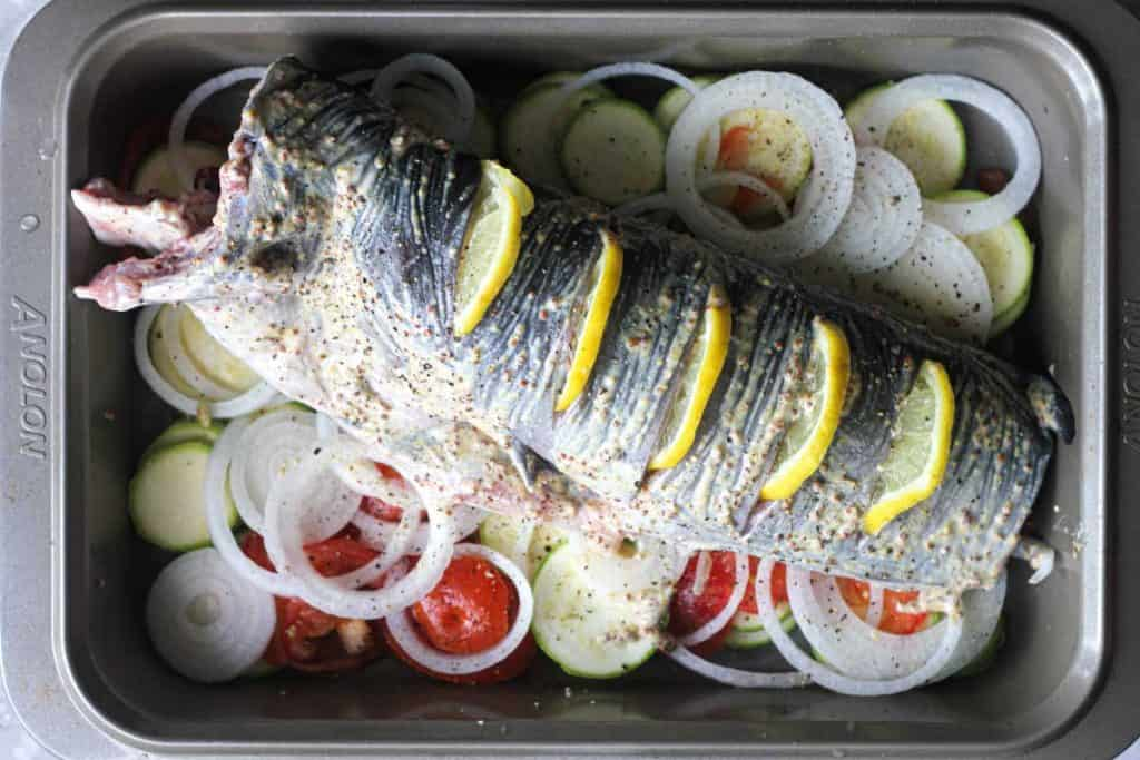 whole catfish on sliced vegetables in the baking tray