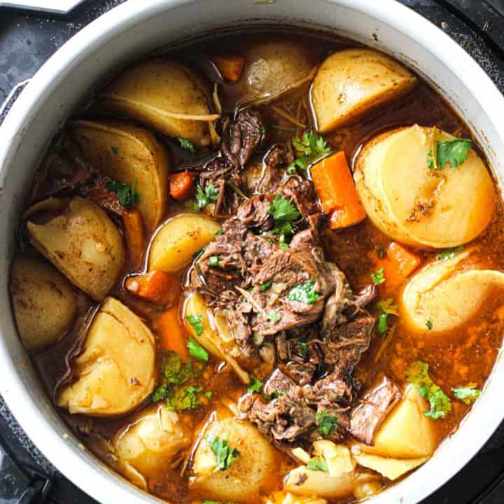 coked beef pot roast in pressure cooker with potatoes and carrots