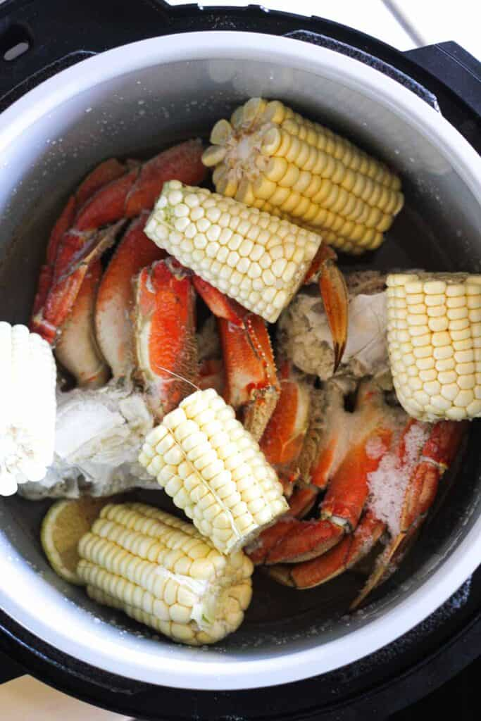 raw corn on the cob and frozen crab in pressure cooker
