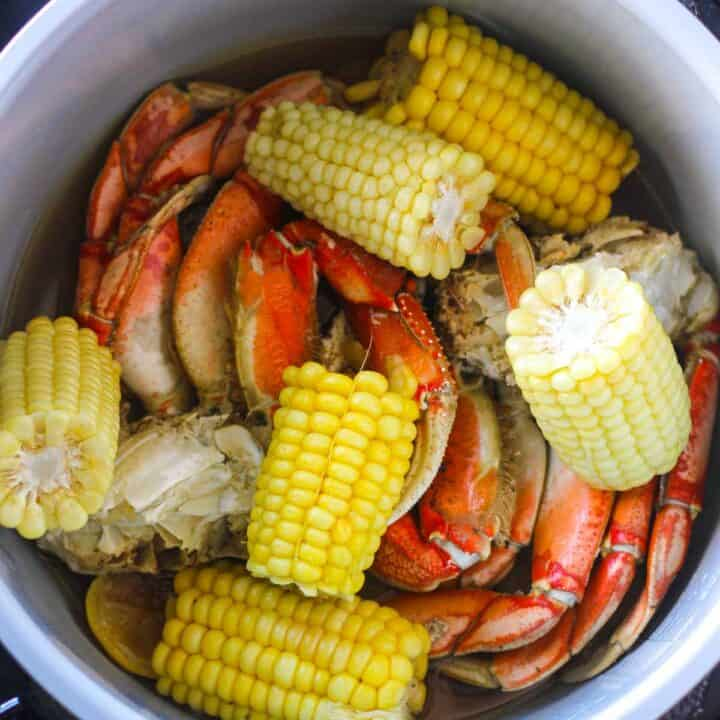cooked corn on the cob and crab legs in pressure cooker
