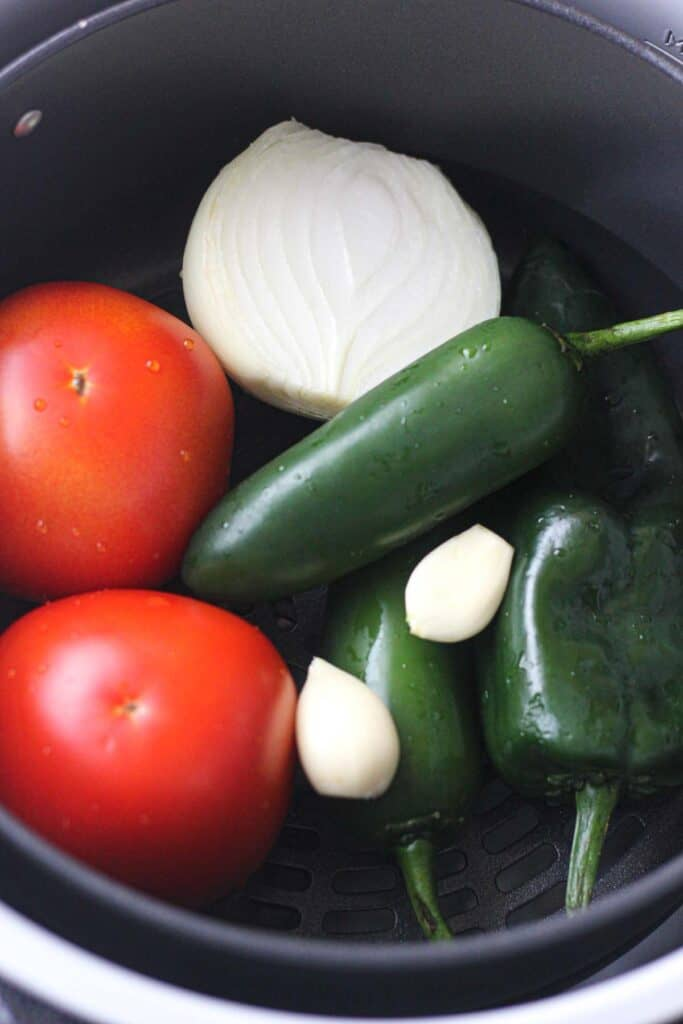 fresh tomatoes, pepers, onions and garlic in the ninja foodi air fryer basket
