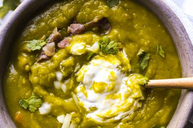 a bowl of split pea soup with cilantro and sour cream on top