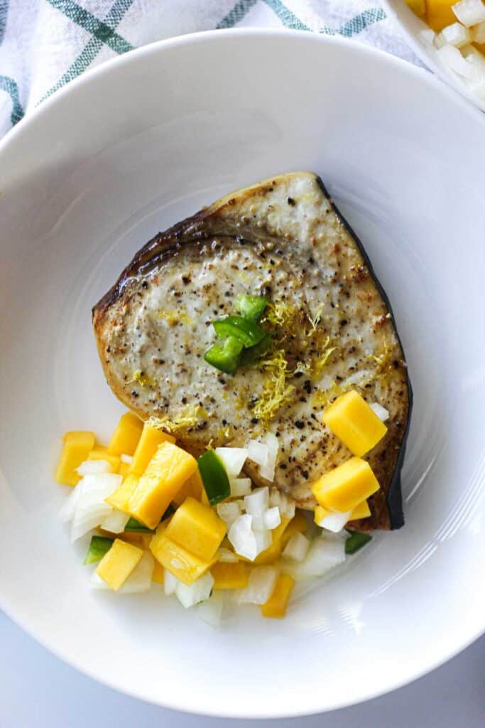 swordfish steak with mango citrus salsa on the white plate