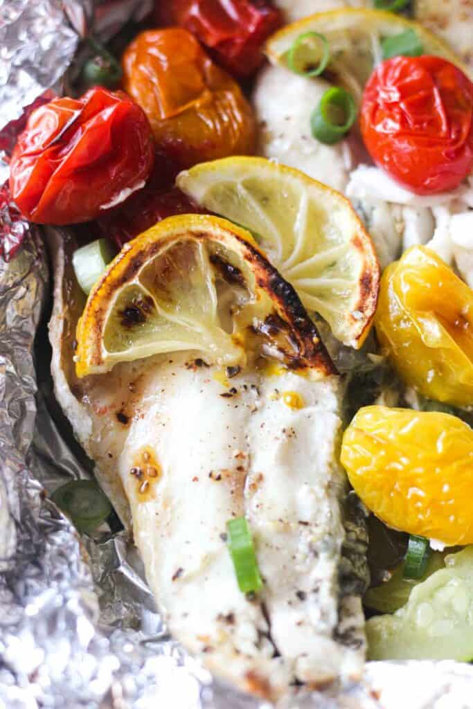 close picture of branzino fish with roasted cherry tomatoes on top