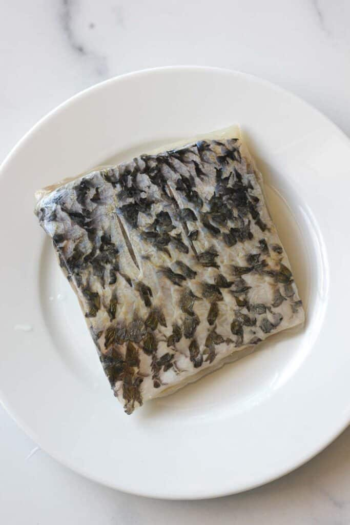 raw skin on barramundi fillet on a plate