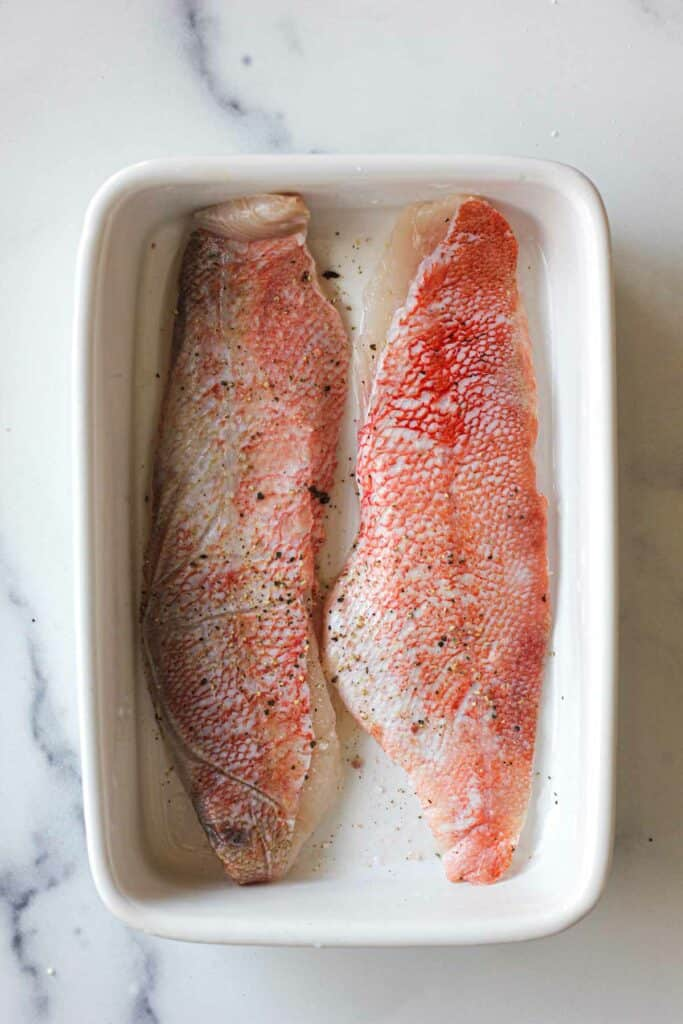 raw skin on ocean perch fillets in a white baking dish