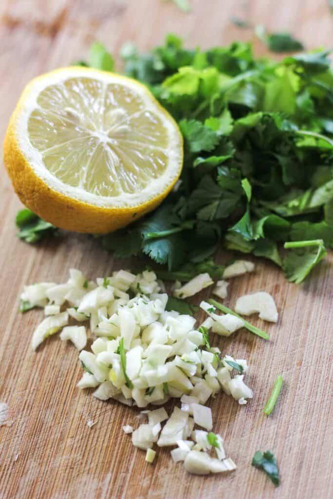 chopped garlic, lemon and cilantro on a cutting board