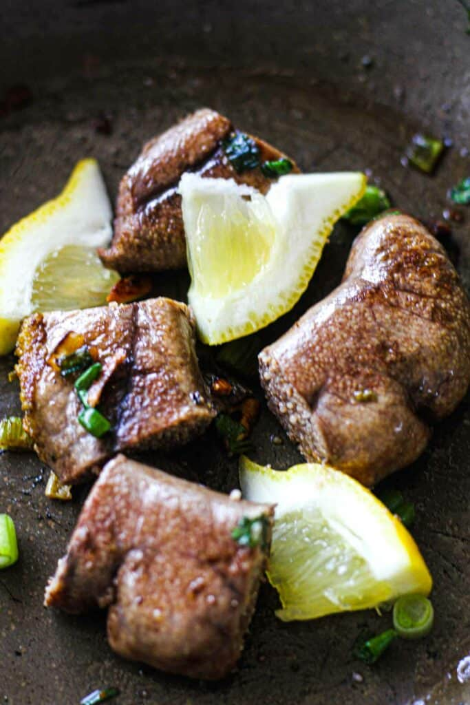 fried shad roe with lemons in a pan