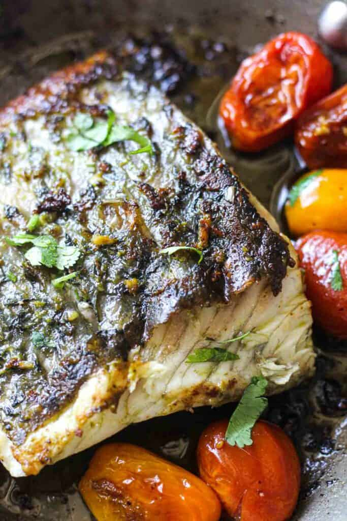 seared barramundi fillet with cherry tomatoes in a pan