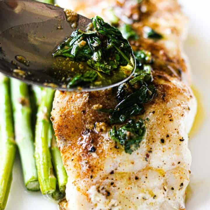 grouper with asparagus on a white plate topped with cilantro butter