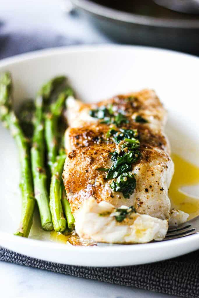pas seared grouper on a white plate with lemon butter sauce