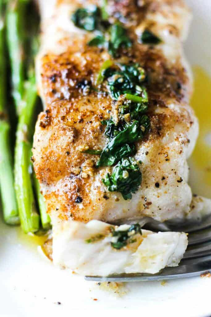 a slice of pan fried grouper fillet with asparagus