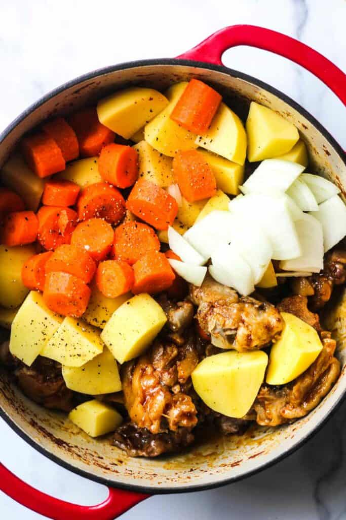 raw carrots, onioins and potatoed on top of pig in the pot