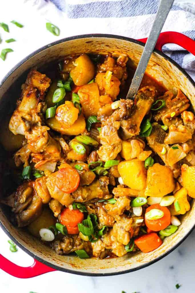 cooked pork feet stew with vegetables in the pot with chopped green onions on top