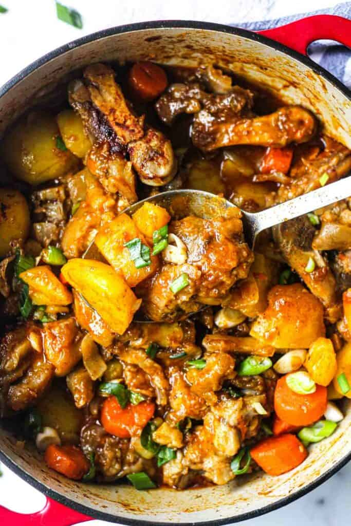 cooked pig feet stew with vegetables in the pot with chopped green onions on top