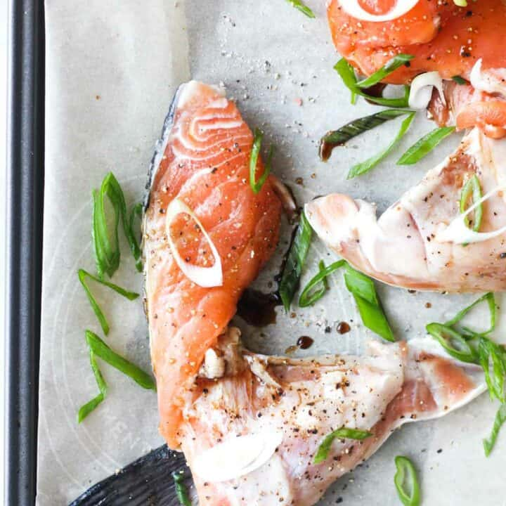 raw salmon kama with chopped scallions on the parchment paper
