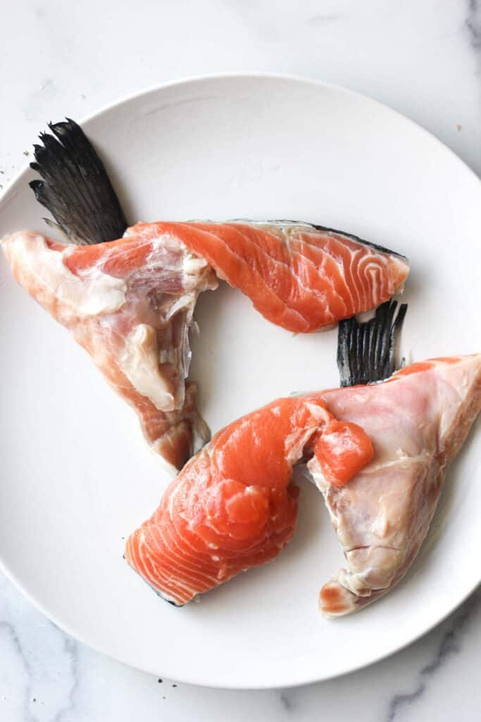 two raw salmon collars on the white plate
