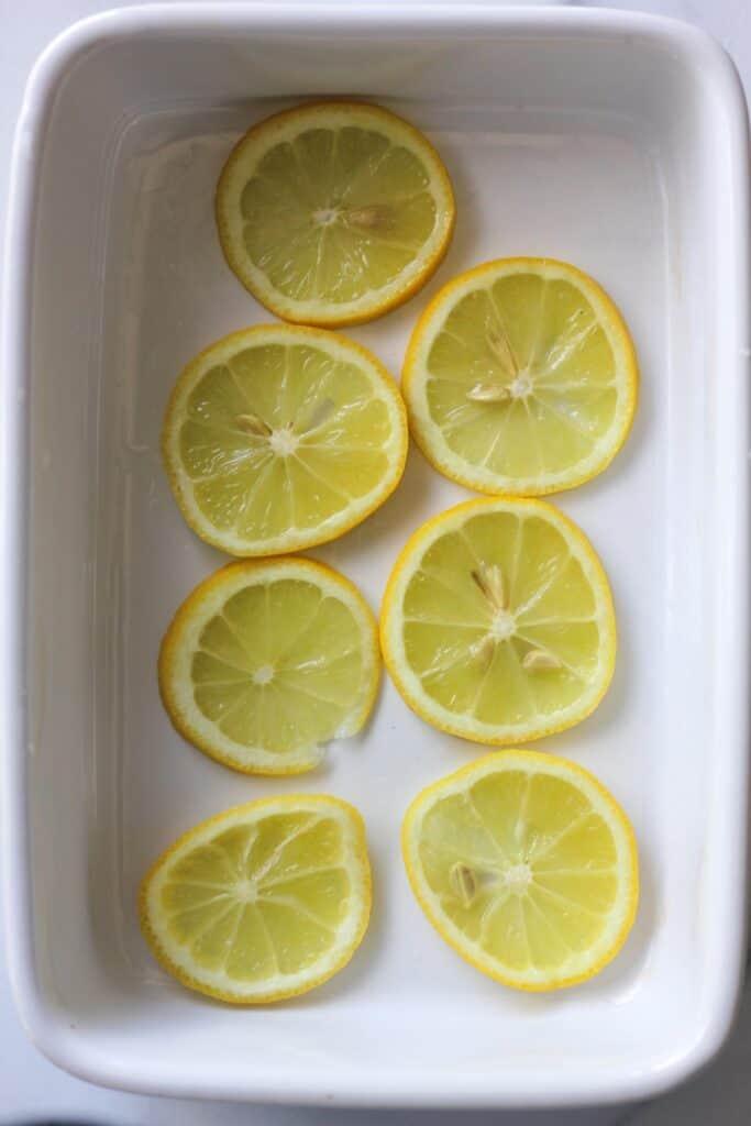 sliced lemons on white baking tray