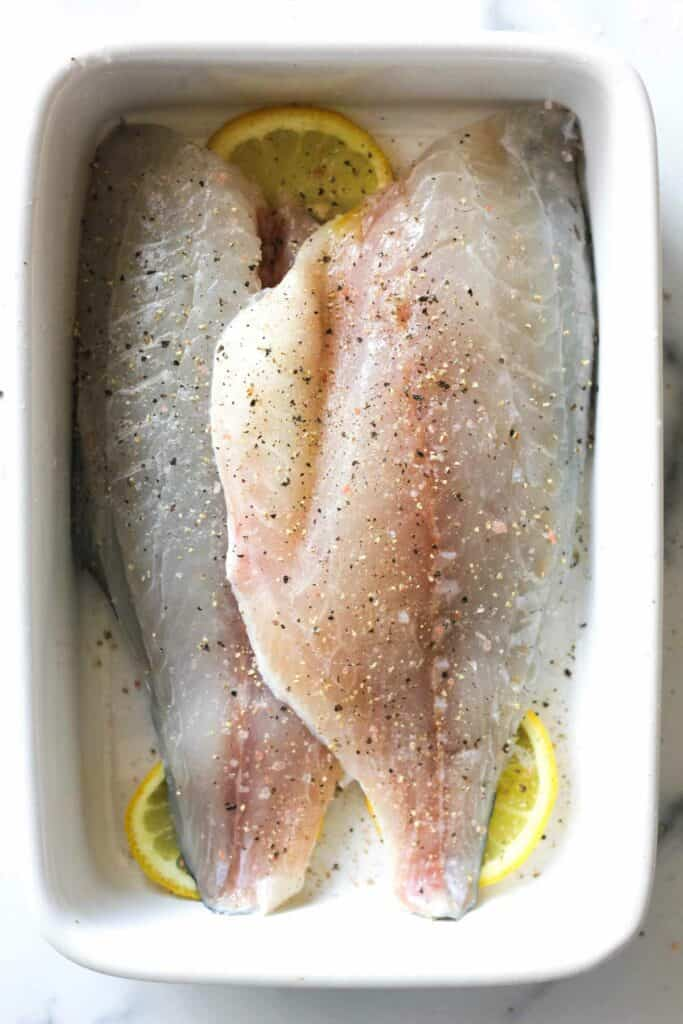 sea bream with lemon slices in a baking dish
