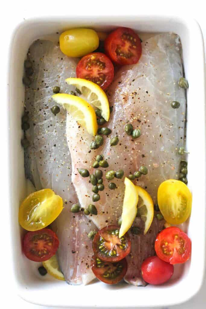 raw dorade fillets with cherry tomatoes, lemon slices and capers