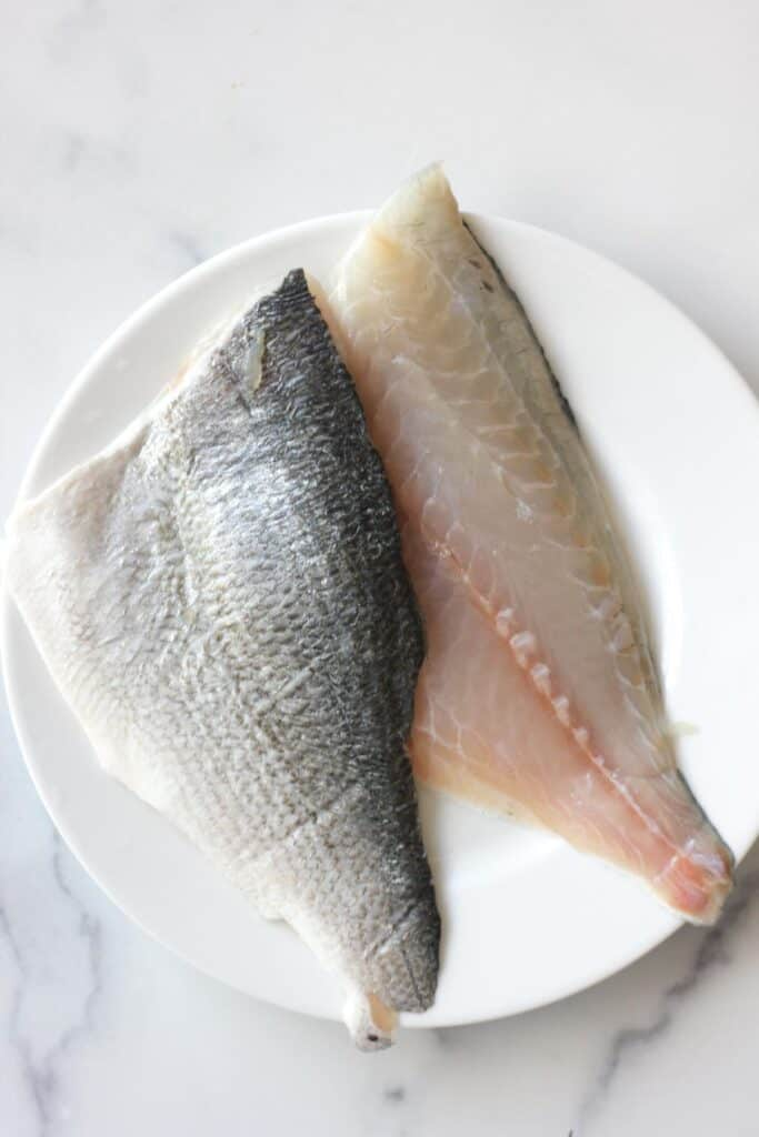 raw sea bream fillets with skin on on the white plate