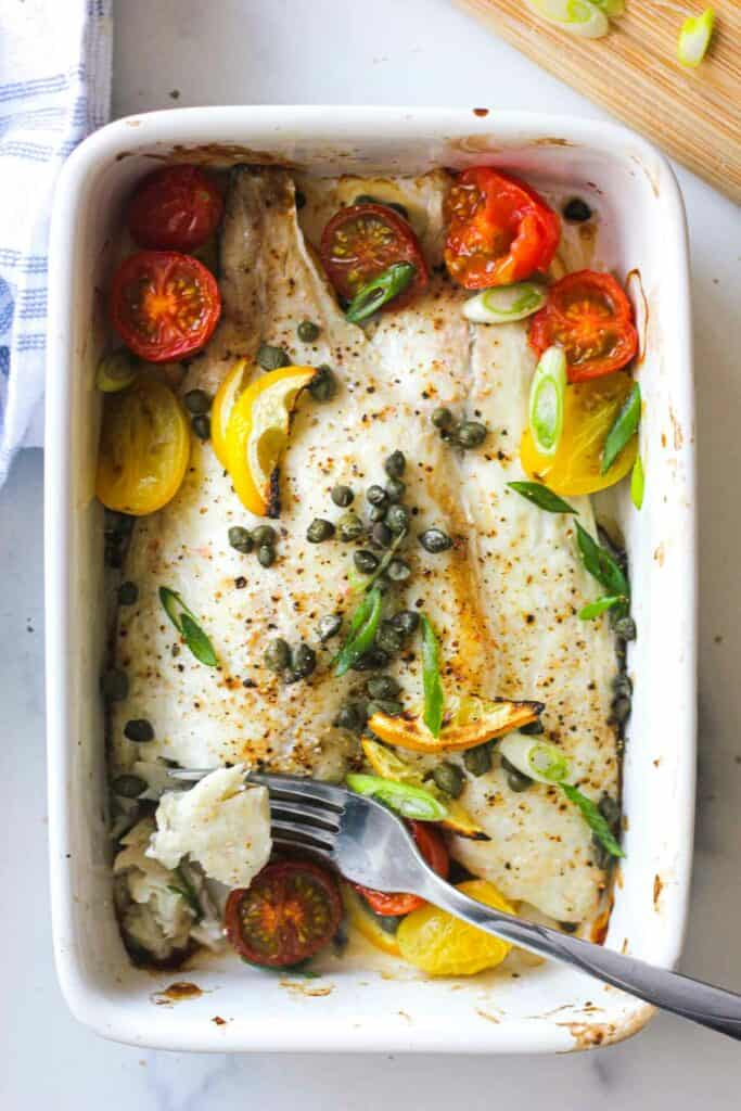 cooked seabream fillets on a ceramic baking plate with a fork
