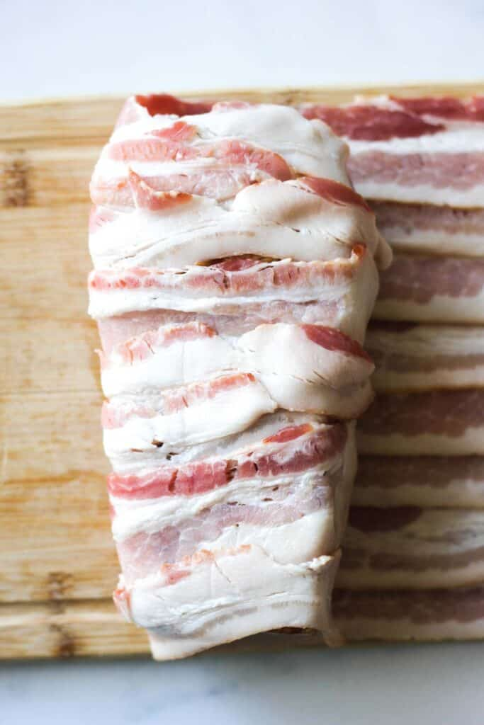 process of wrapping pork in bacon