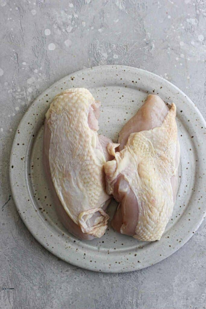 raw skin on chicken breast on a plate