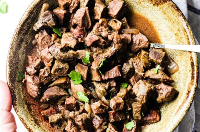 beef heart stew in a brown bowl with chopped parsley on top