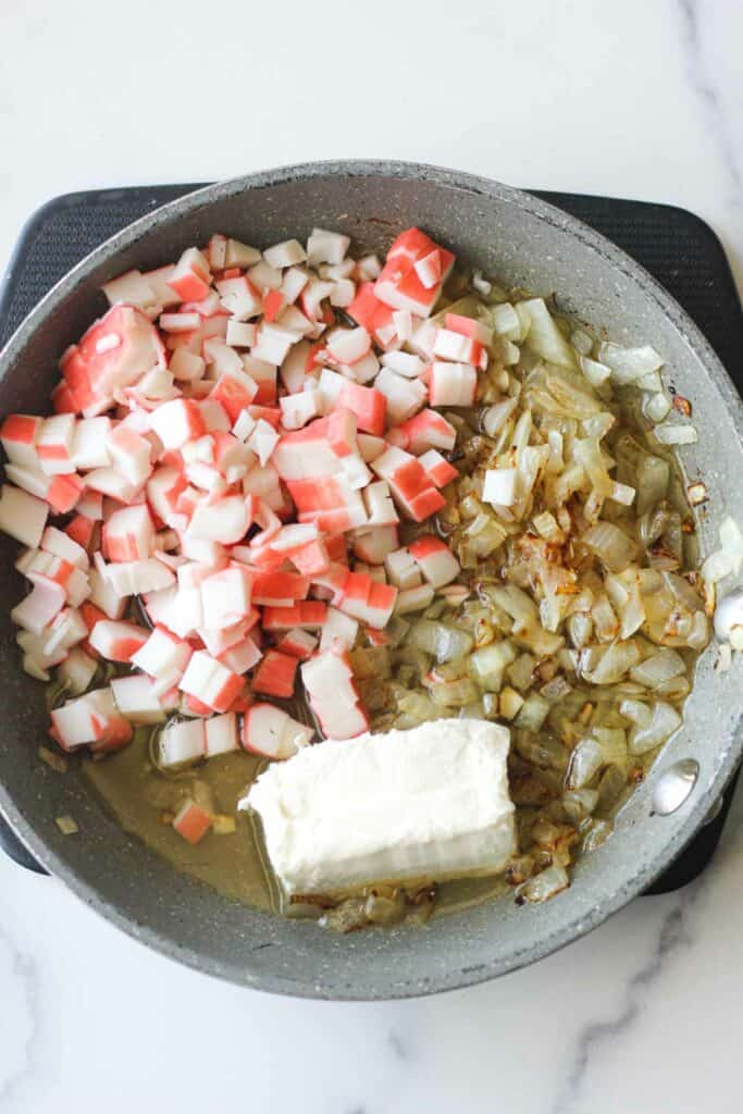 sauteed chopped onion, cream cheese and chopped imitation crab in the pan