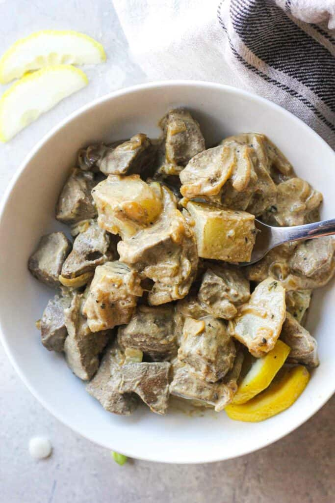 cooked pork liver with potatoes and onions in creamy sauce with lemon slices in the bowl