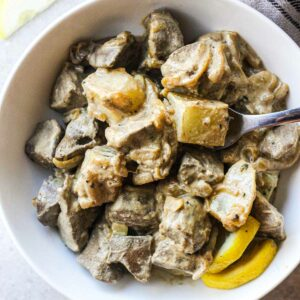 tender sor cream pork liver with vegetables on a plate