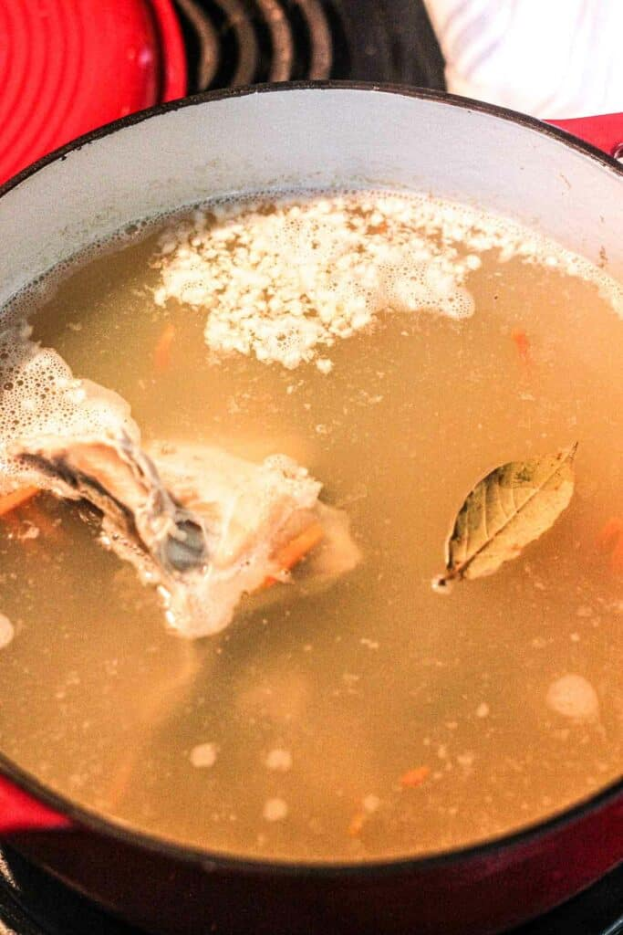 simmering noodle soup with rabbit meat in a red pot
