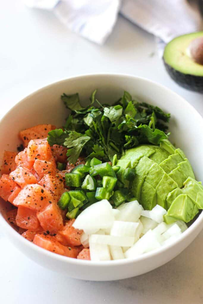 chopped jalapeno, onions, salmon, cilantro and avocado in the white bowl