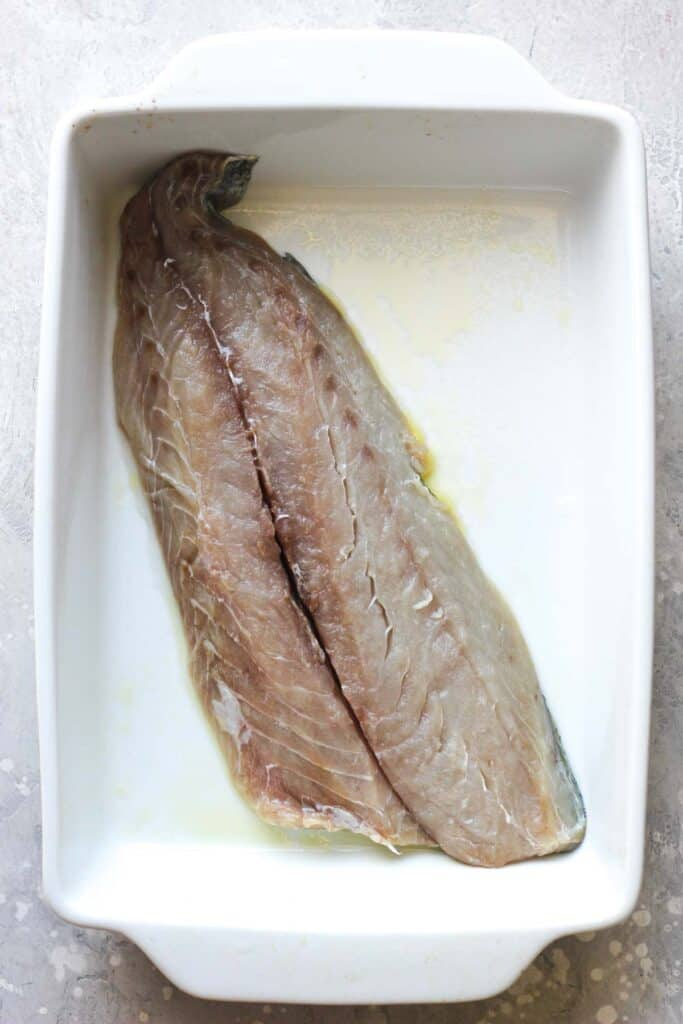 raw fish fillet in a white baking dish