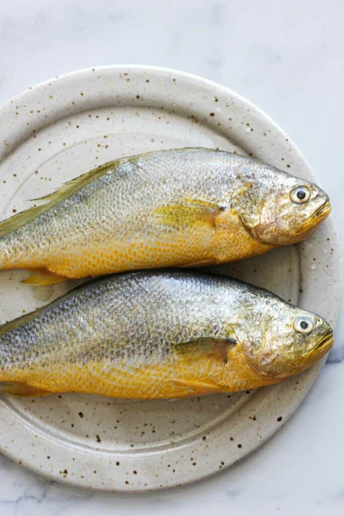 two yellow croaker fishes on the plate