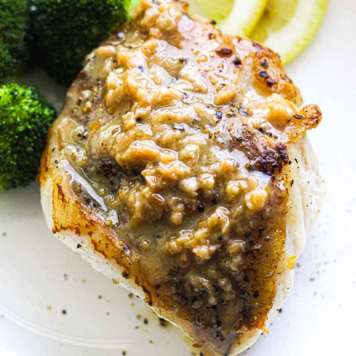 browned monk fish on a white plate with sauce on top