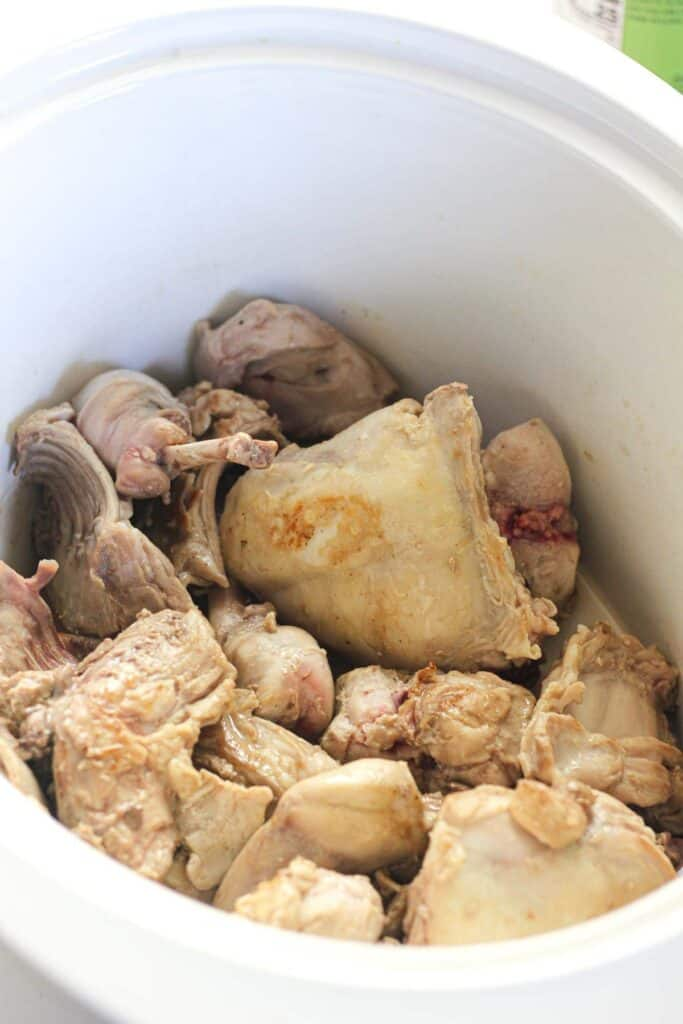 browned rabbit pieces in slow cooker