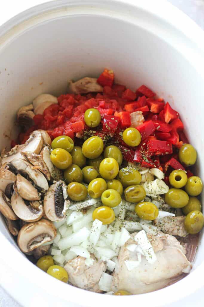 adding green pitted olives to the crock pot on top of other ingredients