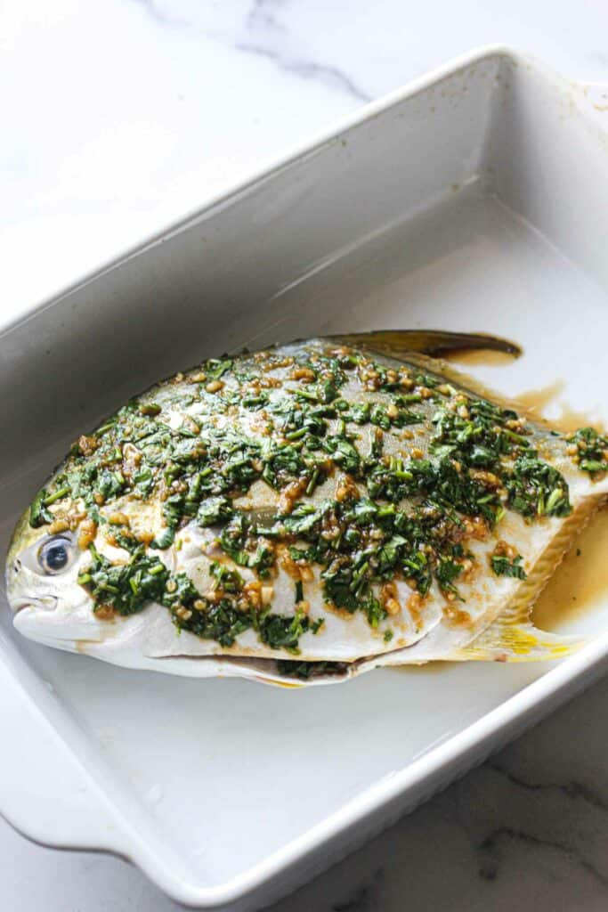 raw whole pompano fish covered in giner, olive oil clantro mixture