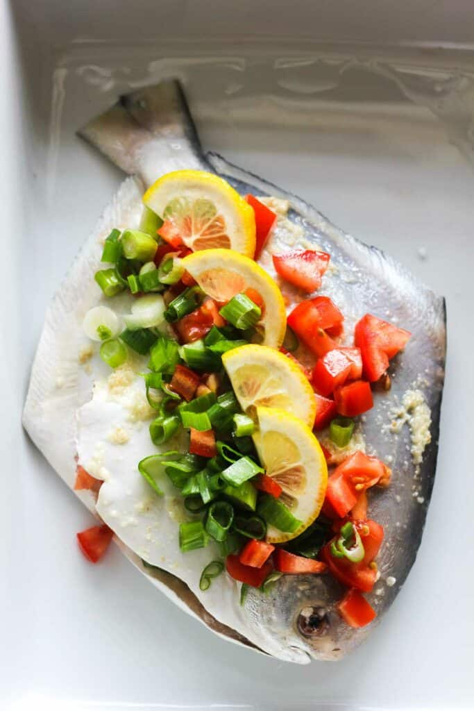 raw pomfret fish covered with tomatoes, green onions and lemon slices