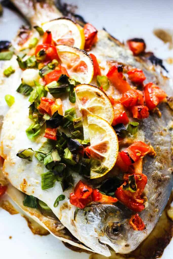 baked whole fish with tomatoes and lemons
