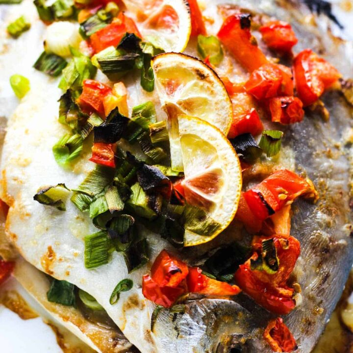 baked fish with green onions on top