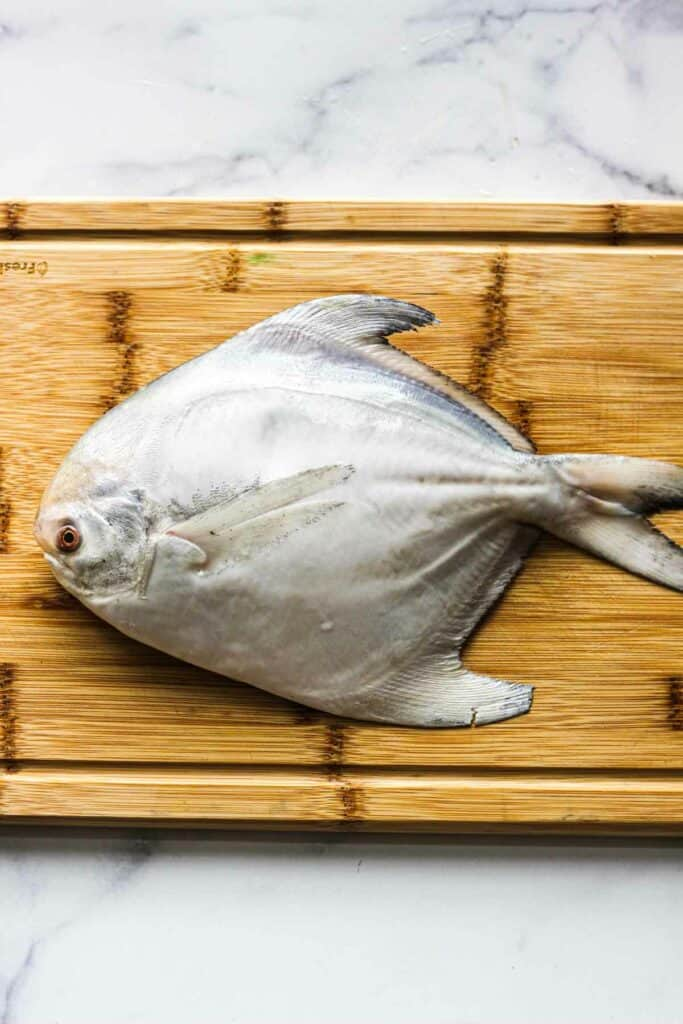 raw whole pomfret on the cutting board before cooking