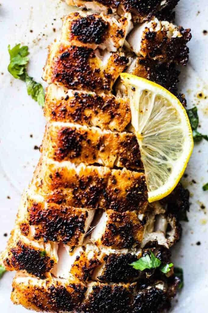 sliced white fish on the plate with lemon