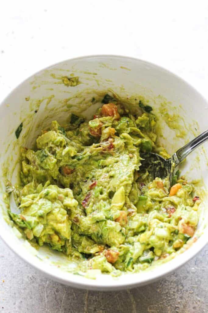 mixing ingredients for the avocado dip in a white bowl with a spoon
