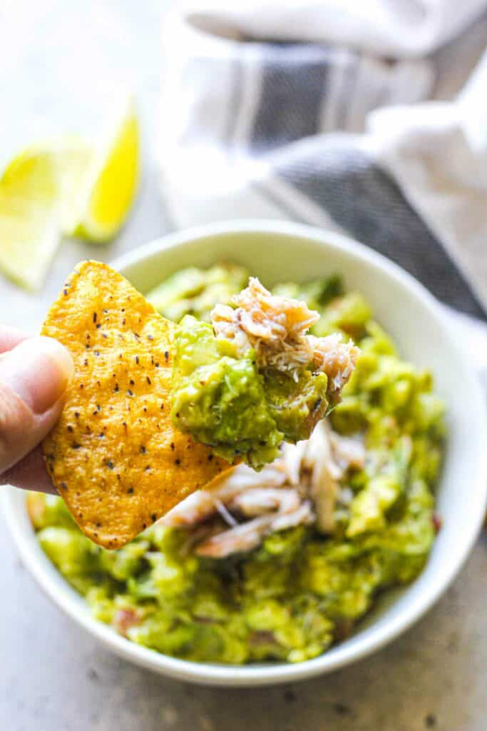 scooped guacamole with crab meat on a tortilla chip