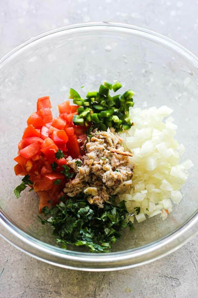 chopped oniona, tomatoes, cilantro, jalapeno and real crab in a glass bowl