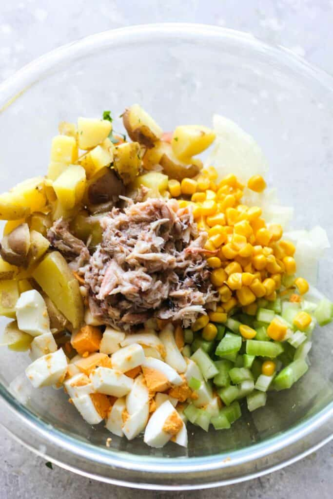 chopped eggs, onions, potatoes, celery, corn and crab on top on the medium glass bowl